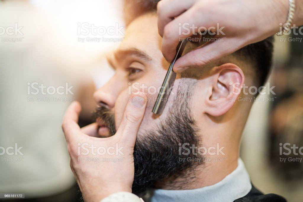 Young man getting his beard freshly cut. zbiór zdjęć royalty-free
