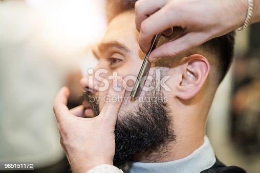 622527180istockphoto Young man getting his beard freshly cut. 965151172