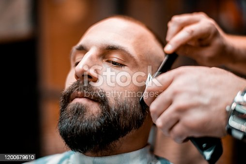 A young bearded man getting his beard shaped with an electric shaver and a comb in a hair salon.