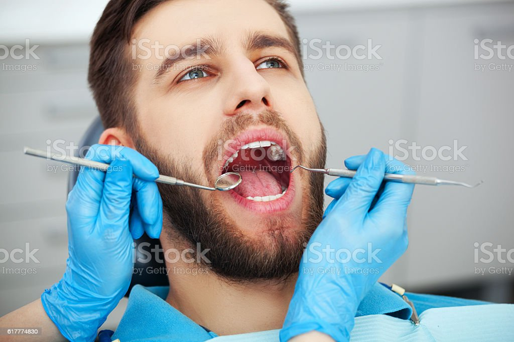 Young man getting his teeth checked by a dentist. stock photo
