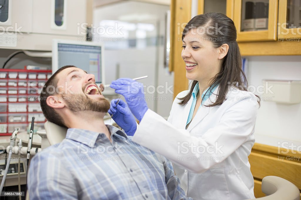Young man getting his teeth cleaned at the dentist. stock photo