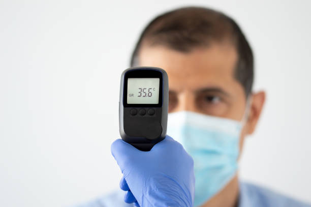 young man getting his temperature taken with an infrared thermometer by a healthcare worker stock photo