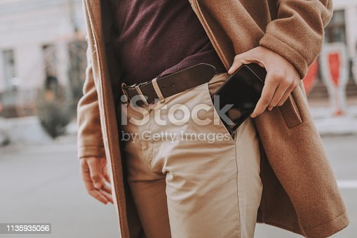 I have to make a phone call. Close up of elegant guy taking modern black cellphone out of trouser pocket