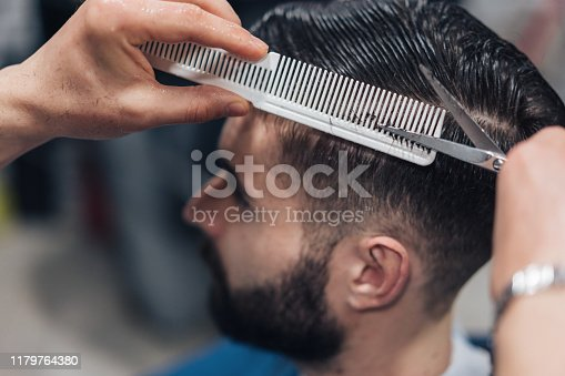 Close-up image of professional barber's hands cutting hair