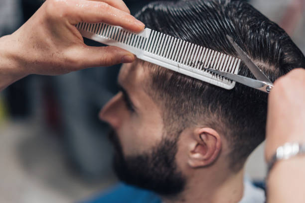 Young man getting stylish haircut stock photo