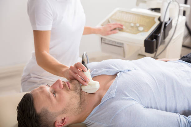 Young Man Getting Ultrasound Of A Thyroid Young Man Lying On Back Getting Ultrasound Of A Thyroid In A Clinic anode stock pictures, royalty-free photos & images