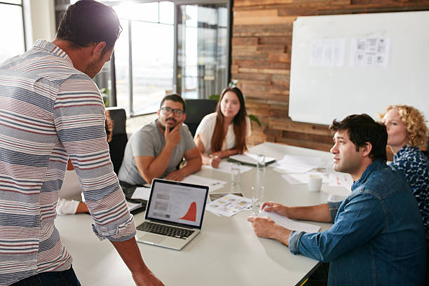 joven hombre dando una presentación a sus colegas de negocios - oficina de empleo fotografías e imágenes de stock