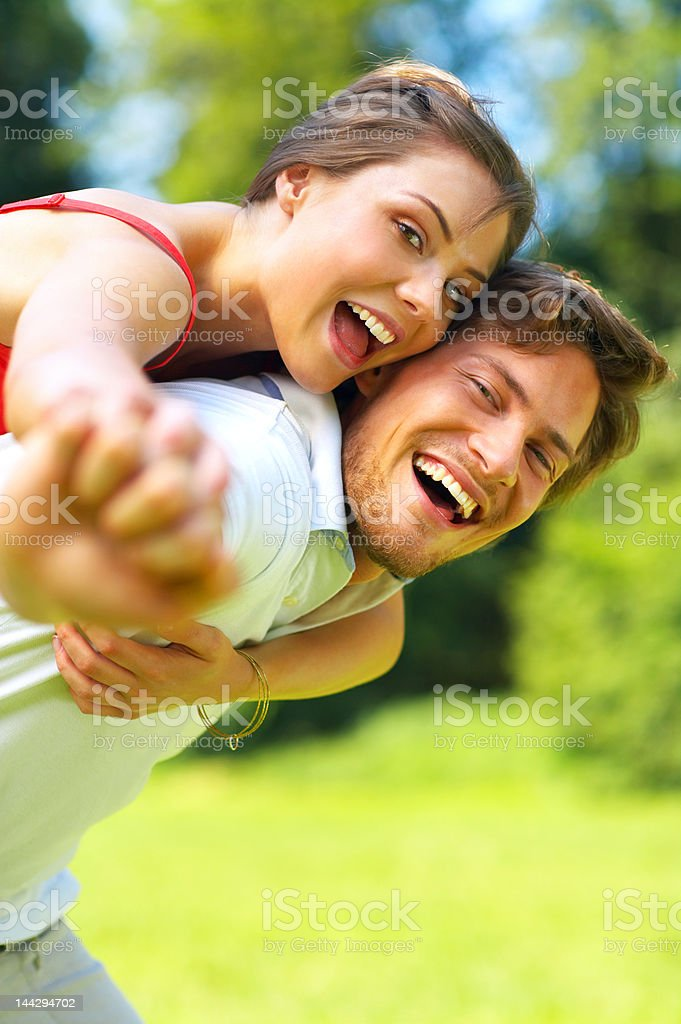 Young man giving his girlfriend a piggyback ride royalty-free stock photo