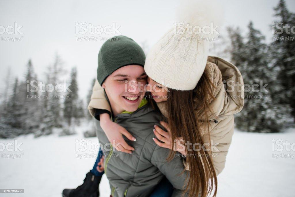 Young man giving his girlfriend piggyback ride stock photo