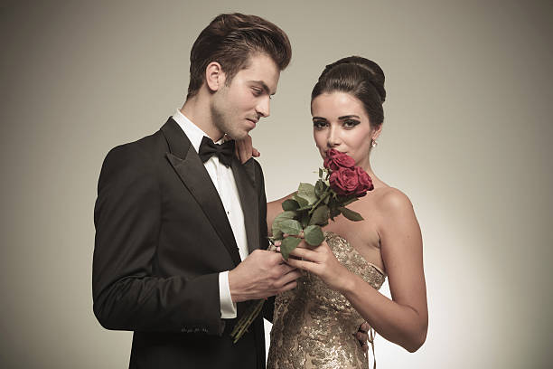 young man giving his wife a bunch of red roses - knotenkleid stock-fotos und bilder