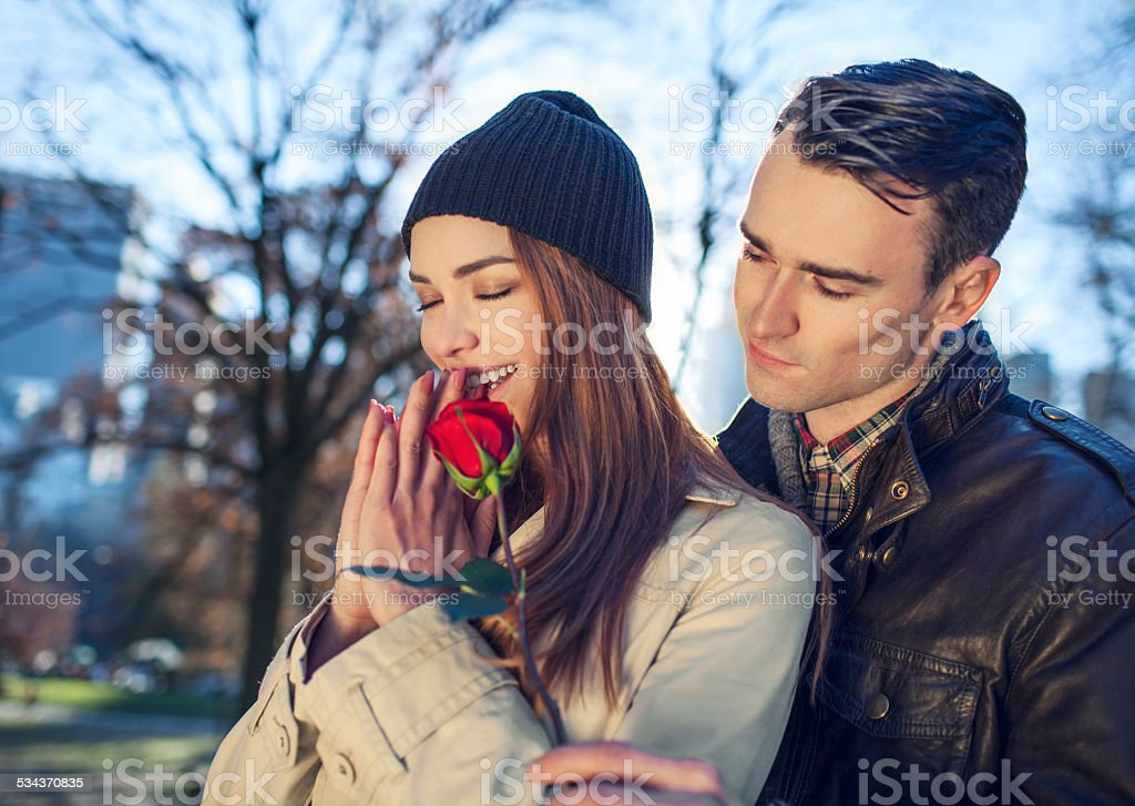 Young man giving rose to woman on a blind date stock photo