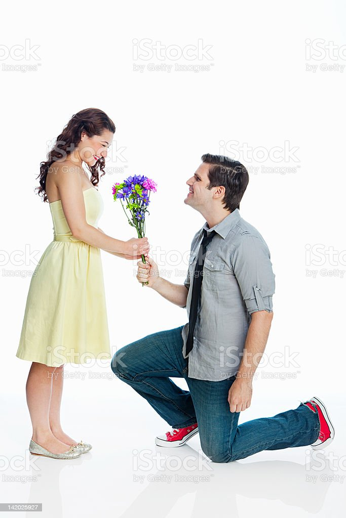 Young man giving woman flowers against white background stock photo
