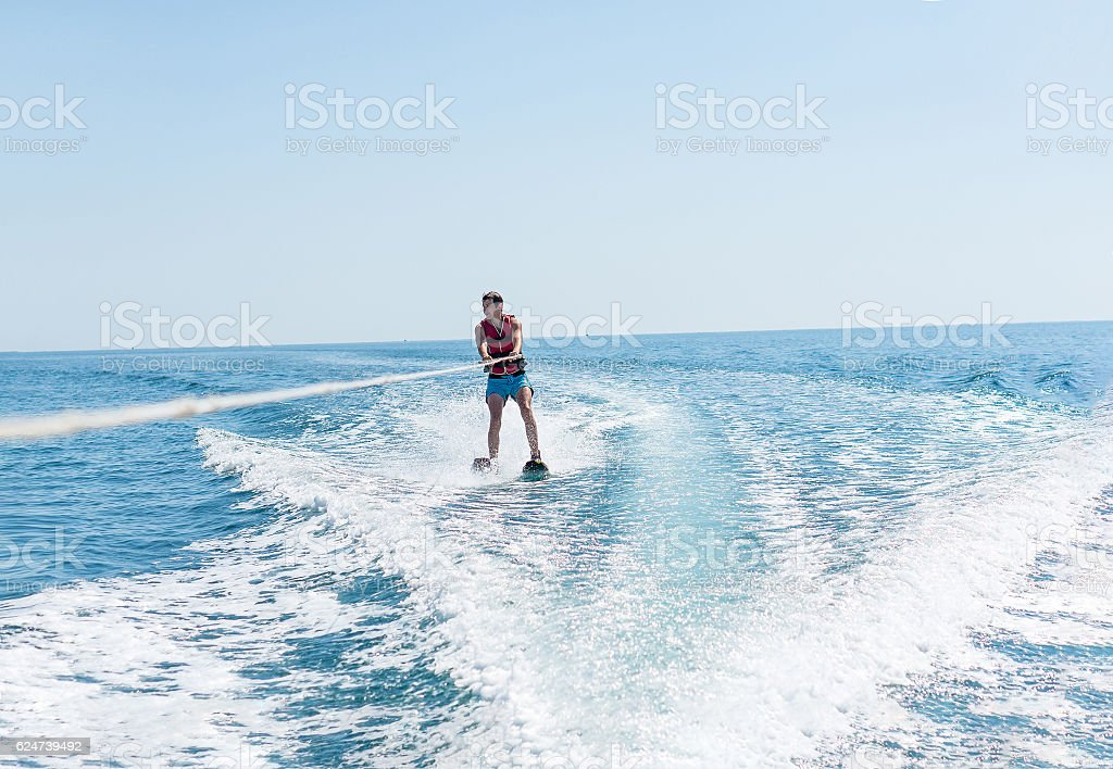 Young man glides on water skiing on the waves stock photo