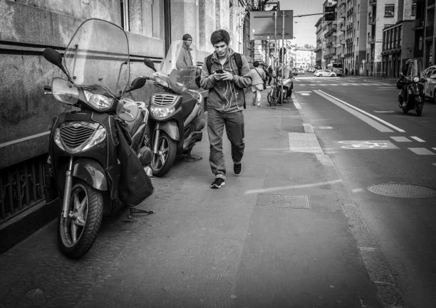 young man goes by the italian street and chatting using the mobile phone in milan, italy - giovani motorino italia parlano foto e immagini stock