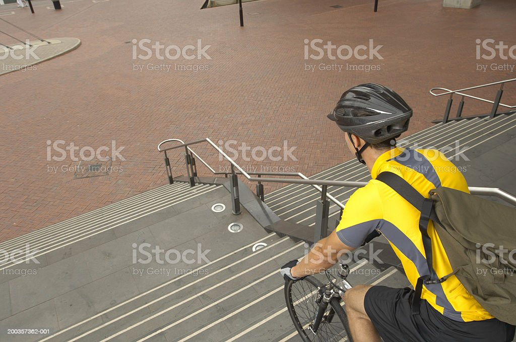 Young man going down steps on bike, rear view, elevated view royalty-free stock photo