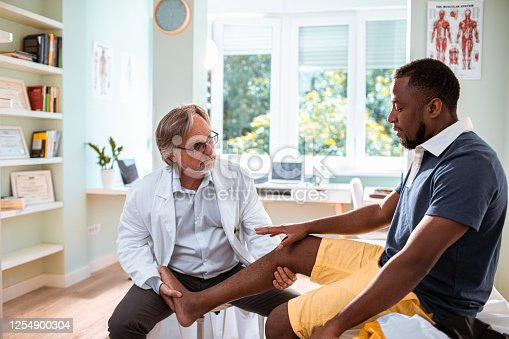 Close up of a doctor having an appointment with a patient with leg pain