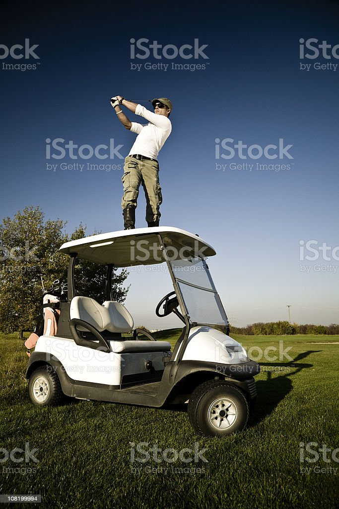 Young Man Golfing off the Roof of Golf Cart royalty-free stock photo