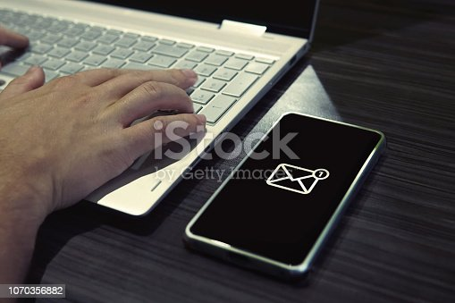 519520560istockphoto Young man got one new message on phone while typing on laptop. Generic icon of mail on black-screened smartphone lying on the office table close to a working man. Getting messages while being online. 1070356882