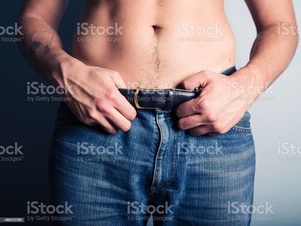 Young man grabbing his belt stock photo