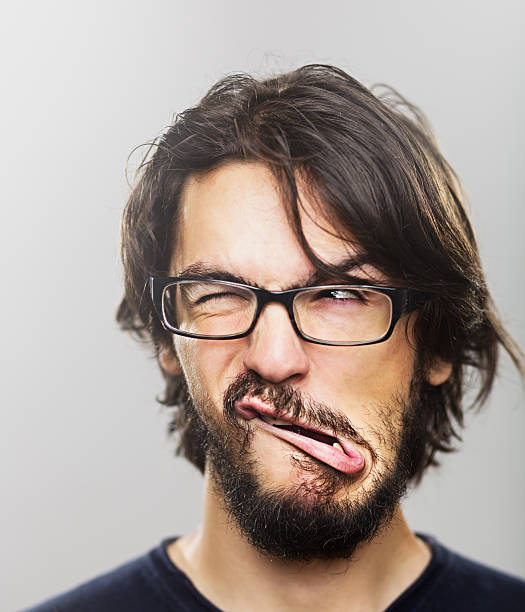 Young man grimacing Portrait of a young man with a beard winking and making a face. grimacing stock pictures, royalty-free photos & images