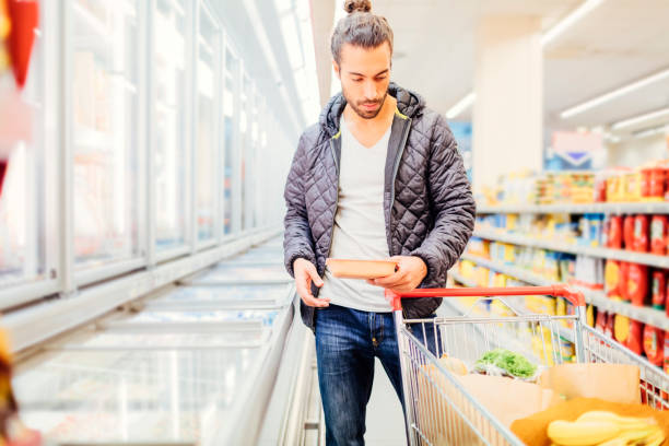 Young Man Groceries Shopping Young Man Groceries Shopping. Standing in front of refrigerated section and choosing frozen food man bun stock pictures, royalty-free photos & images