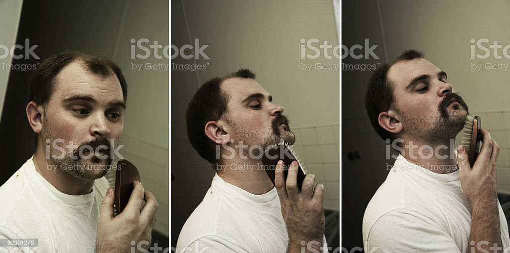 Young Man Grooming his Mustache and Beard royalty-free stock photo