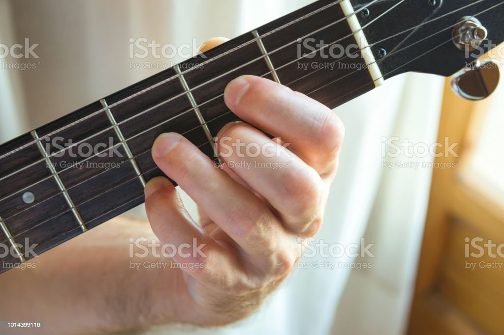 Young Man Guitarist Holding Fret Board Of Guitar Playing Chord By ...