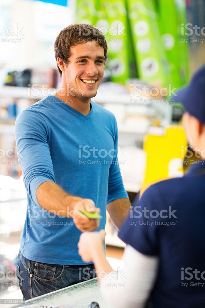 young man handing over credit card to a female cashier stock photo