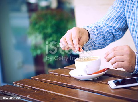 Young man hands holding sugar bag and sweetens coffee in a cafe.