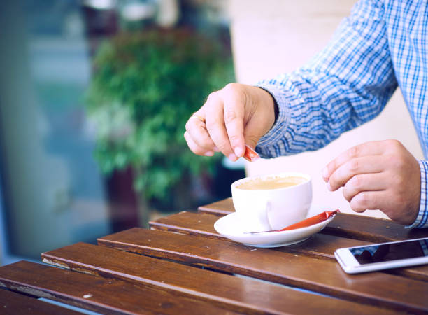 young man hands holding sugar bag and sweetens coffee in a cafe. - sweeteners stock photos and pictures