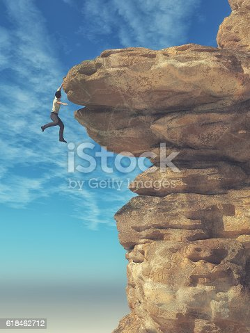 istock Young man hanging from a cliff 618462712