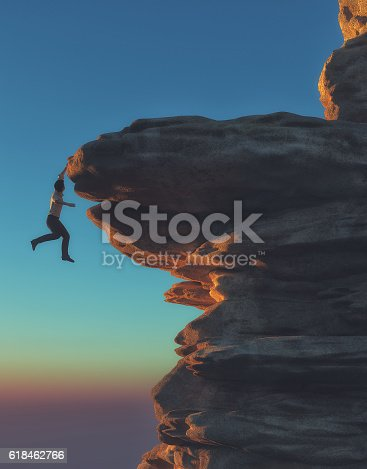 istock Young man hanging from a cliff 618462766