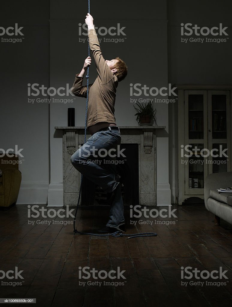 Young man hanging from rope in living room 免版稅 stock photo