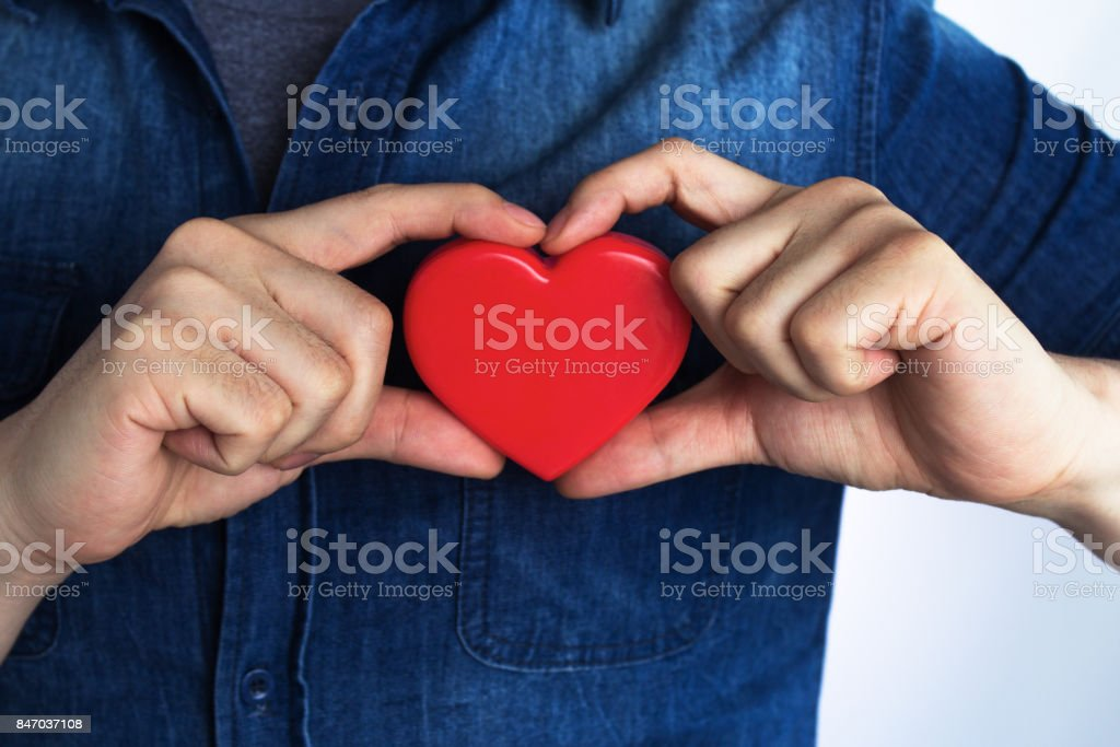A young man has a red heart shape on his chest by hand.(World heart day,Valentine's day,Love) stock photo