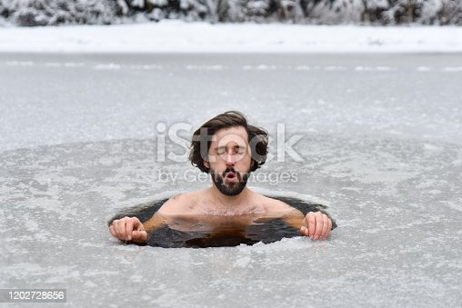 istock Young man have bath in cold water in nature and does Wim hof method 1202728656