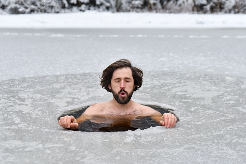 Young man have bath in cold water and does Wim hof method outdoor