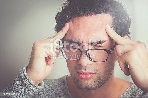 626964348istockphoto Young man having a bad headache 865867578