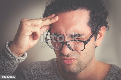 626964348istockphoto Young man having a bad headache 883308332