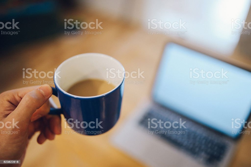 Young man having a coffee and working at home stock photo
