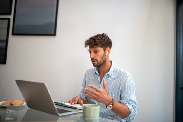 Young man having a conference call stock photo