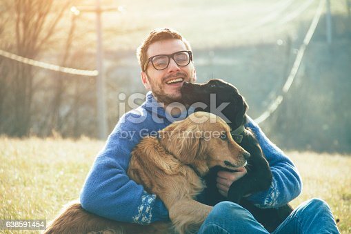 istock young man having a fun with dogs in the nature 638591454