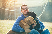 young man having a fun with dogs in the nature