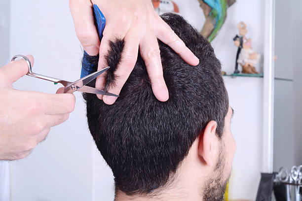 Young man having a haircut with scissors. stock photo
