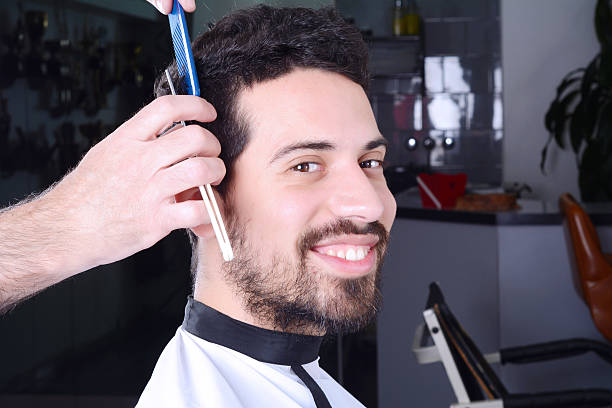 Young man having a haircut with straight razor. stock photo