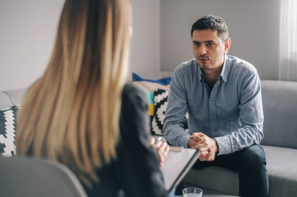 Young man having a home meeting with counsellor stock photo