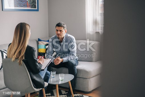 Young man having meeting with counsellor. They are sitting and talking in his living room