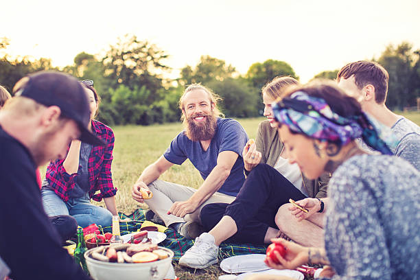 Young man having a picnic with friends in park stock photo