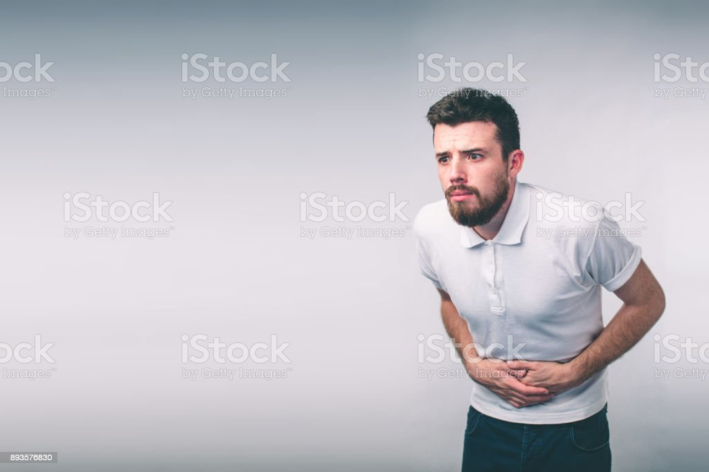 young man having a stomachache..Close up of male body isolated on White Background. stock photo
