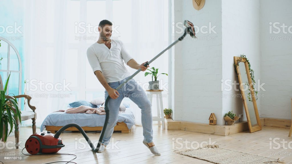 Young man having fun cleaning house with vacuum cleaner dancing like guitarist stock photo