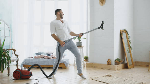 Young man having fun cleaning house with vacuum cleaner dancing like guitarist Dancing young man having fun cleaning house with vacuum cleaner at home cleaning equipment stock pictures, royalty-free photos & images